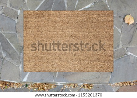 Blank doormat before the door in the hall. Mat on ceramic floor, flowers and red shoes. Welcome home, product Mockup - Shutterstock ID 1155201370
