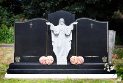 Blank elaborate gravestones with jesus figure in between and flowers at base. Beautiful marble double headstones.