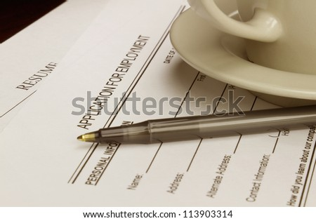 Blank employment application with resume, pen and coffee on desk.