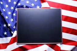 Blank empty black chalkboard with copy space for text on American flag background. United States of America stars & stripes patriot remembrance symbol. Template for greetings or ad. Close up, top view