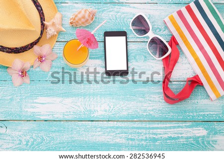 Blank empty tablet computer on the beach. Trendy summer accessories on wooden background pool. Sunglasses, orange juice and flip-flops on beach. Tropical flower orchid. Flat mock up for design.