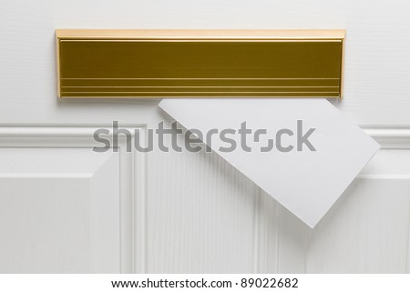 Blank envelope posted through copper letter box in white door