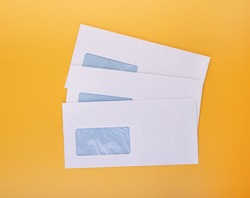 Blank envelopes with address window on yellow background. White paper envelopes mockup for business correspondence, postal stationery and corporate lettering