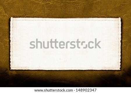 Blank fabric label on leather background close up