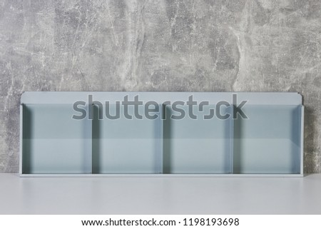 Blank flyer mockup glass plastic transparent holder against gray wall background. Plain flier stand. Clear brochure holding. Clean sheet mock up design presentation. Shows flyers.  #1198193698