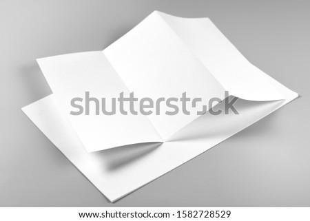 Blank Folded Flyer or Letterhead over Stack of Paper Stockfoto ©