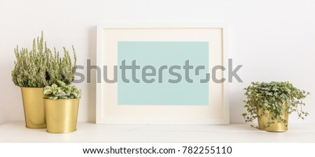 Blank frame and a plants in golden pots on a shelf. Modern home decor. Mock up.