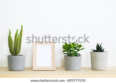 blank frame and cactus pot on table at home  - Shutterstock ID 689379550