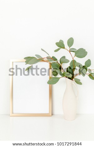 Blank frame mockup with a branches of eucalyptus in vase on table on light background. Home decor. Blog, website or social media concept.
