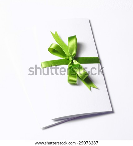 Blank gift tag tied with a bow of green satin ribbon. Isolated on white, with soft shadow