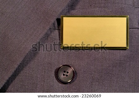 Blank gold and brass name tag on corporate business man suit jacket breast pocket with empty copy space for text insertion