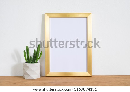 Blank gold frame poster on table with cactus plant