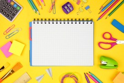 Blank graphing paper notebook with school supplies frame against a yellow background. Back to school concept. Copy space.