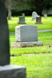 Blank graveyard headstone with no name, more headstones in background, out of focus, green grass, cemetery, death, burial marker, tombstone, bury, life insurance, pandemic, coronavirus, covid