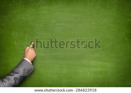 Blank green blackboard with businessman hand pointing