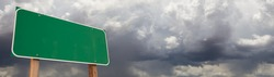 Blank Green Road Sign Against Ominous Cloudy Stormy Sky Background Banner.