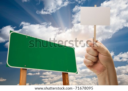 Blank Green Road Sign and Man Holding Poster on Stick Over Blue Sky and Clouds.