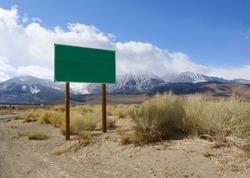 Blank green road sign board in rural area