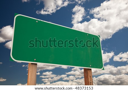 Blank Green Road Sign on Dramatic Blue Sky with Clouds - Ready for your own message.