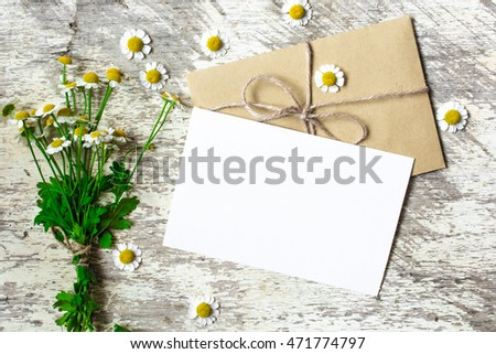 Blank greeting card and envelope with white chamomile flowers on white rustic wood background for creative work design #471774797