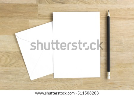 Blank greeting card mockup with pencil on wooden table #511508203