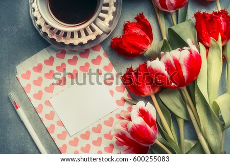 Blank greeting card with hearts and pencil , pretty tulips and cup of coffee, top view.  Mothers Day concept #600255083
