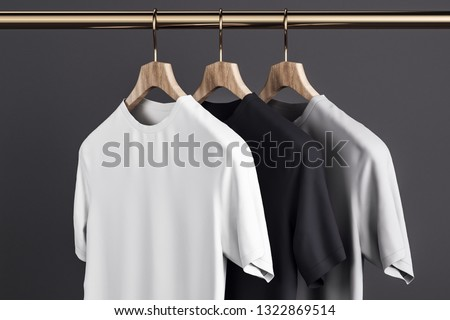 Blank grey, white and black t-shirts on hanger. Concrete wall background. Design, store and style concept. Mock up, 3D Rendering