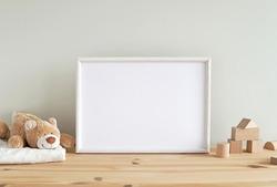 Blank horizontal frame mockup, nursery framed wall art, baby room art, empty frame for print, photo, wooden shelf, baby toys and blanket.