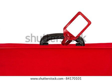 Blank identification tag on handle of red suitcase. Closeup over white