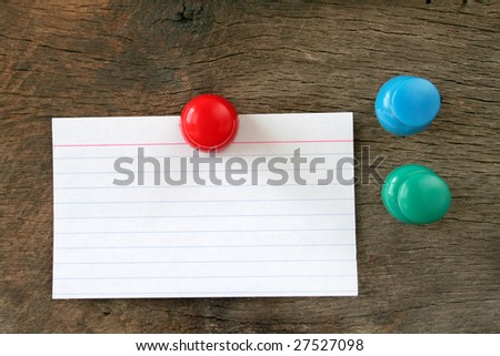 Blank index card hung on a piece of wood with a stick pin.