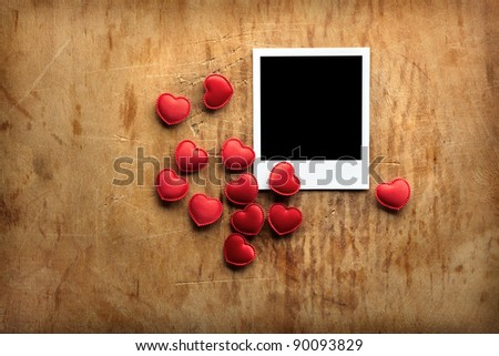 Blank instant photo and small red hearts on old dark grunge background.