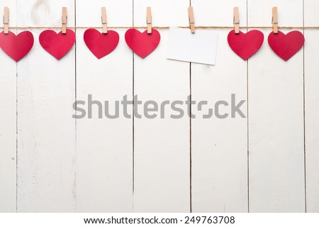 Blank instant photo and small red paper heart hanging on the clothesline. On white wooden background. Love heart hanging on wooden texture background, valentines day card concept