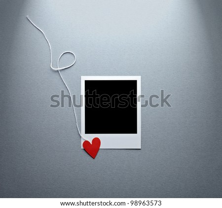 Blank instant photo and small red paper heart with white rope. On textured paper background.