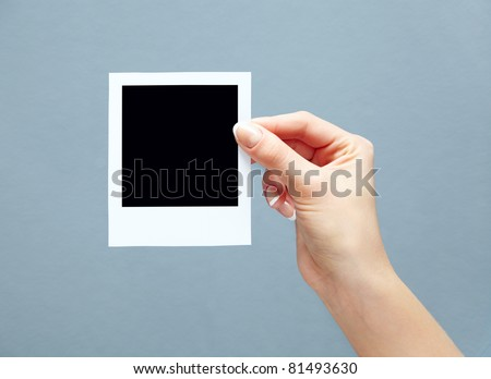 Blank instant photo in woman's hand - place your own picture on it. Close-up. - stock photo