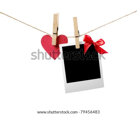 Blank instant photo with red bow and red paper heart hanging on the clothesline. Isolated on white. - stock photo