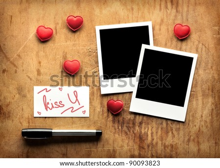 Blank instant photos and small red hearts with blank business visit card and fountain pen on old dark grunge background