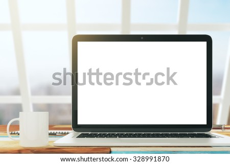 Blank laptop with cup of coffee in a sunny loft interior, mock up