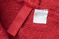 Blank laundry care clothes label on red knitted fabric texture background