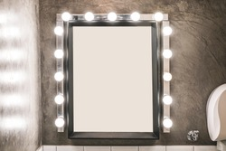 Blank makeup mirror with light bulbs on a concrete wall in a toilet