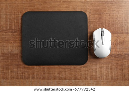Blank mat and wireless mouse on wooden background #677992342