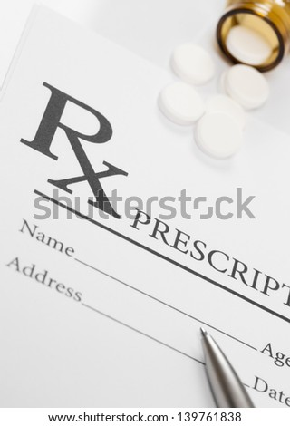 Blank medical prescription, pills and pen on table