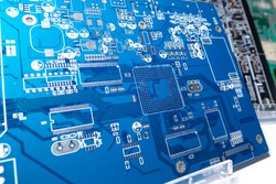 Blank motherboard for a computer. Blue circuit board close up. Motherboard computer board without processors. PCB without additional elements. Several PCBs stand side by side. PCB on a shop window