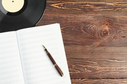 Blank music notebook and vinyl plates. Notebook for musical notes with blank sheets, vinyl record, pen and copy space. Concept of musical education.