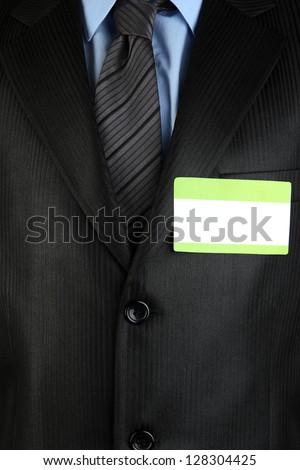 Blank nametag on businessman's black suit close up