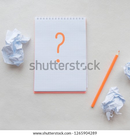 Blank note paper with pencil. Opened notepad. Around the notepads lies lot crumpled paper. Solve the problem. Workplace. Question mark message.