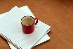 Blank notebook and drunk coffee cup on a ginger background