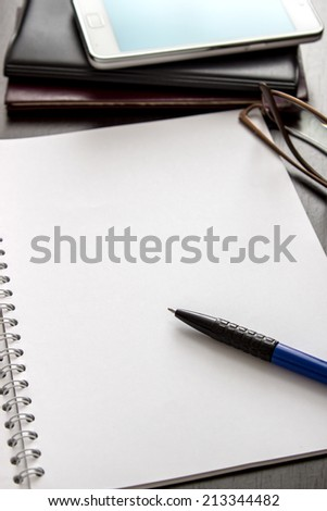 blank notebook and glasses on table, backlit #213344482