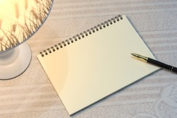 Blank notebook and pen illuminated by desk lamp, night work or study place
