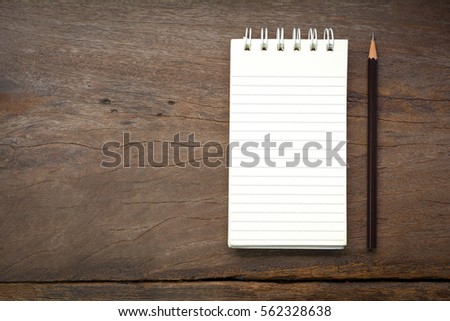 Blank notebook and pencil on wooden background #562328638
