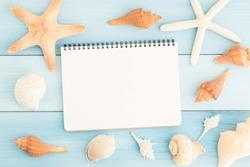 Blank notebook and seashells on blue wooden floor.